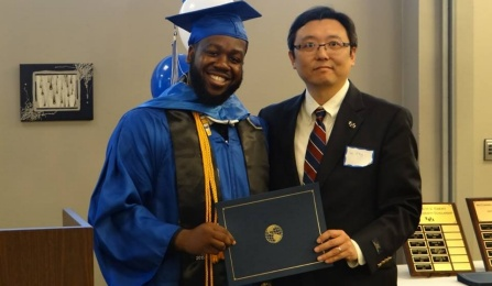 a picture of a UB geography professor Granting award to a student.