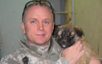 "Portrait of William Mandrick, PhD, on a deployment, with a puppy found after a firefight with al Qaeda insurgents. Puppy was adopted by US forces. Mandrick observes, ""We liked having dogs around because they sense when something is not right."" ."