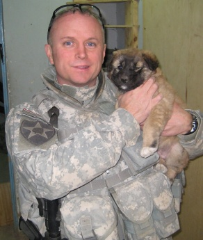 "Portrait of William Mandrick, PhD, on a deployment, with a puppy found after a firefight with al Qaeda insurgents. Puppy was adopted by US forces. Mandrick observes, ""The combat out-posts liked liked having dogs around because they sense when something is not right.""."
