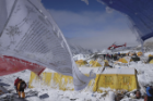 Buddhist prayer flags frame a rescue helicopter taking off from Base Camp. Photo: Roberto Schmidt/AFP/Getty Images