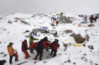 Rescuers use a makeshift stretcher to carry an injured person out of Base Camp. Photo: Roberto Schmidt/AFP/Getty Images