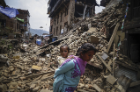 A Nepalese woman carrying her child walks past collapsed buildings in Kathmandu from a second major earthquake (magnitude 7.3) on May 12. Photo: Sunil Pradhan/Anadolu Agency/Getty Images