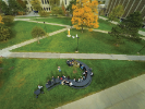 "University Communications' drone camera captures Matthew Hume's class seated at ""Why?"" The 40-by-20 question mark-shaped picnic table can seat about 60 and serves as a place to meet and question things, according to artist Michael Beitz. ""What could be more important at the present moment than to be critical in looking for points of unity and gathering?"" Beitz says."