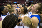 Bulls head coach Felisha Legette-Jack (center) is surrounded by jubilant players after defeating Florida State, 86-65, on its home court.