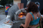A wood-burning pizza oven forms the locus of an outdoor community space between lots.