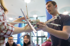 Students prepare their entry in the popular egg drop competition. The idea is to build a contraption that will enable an egg to survive a fall from the third floor of the Student Union to the lobby below.
