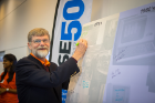 Ed Goit (MS '69, BA '67), a CSE grad from the department's early years, adds his name to a message board at the alumni symposium in September. Photo: Douglas Levere