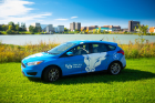 UB Zip Car with spirit mark in front of Lake LaSalle