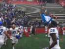 UB Bulls football players waving a UB flag to celebrate their win against Rutgers.