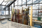 Nicole Clouston incubating columns in UB greenhouse • 2016 • Using soil as its medium, this project involves filling a series of acrylic prisms with mud and nutrients. When exposed to light, microbial life in the mud will flourish in varied layers, creating vibrantly colored bands throughout the sculpture.