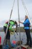 UB geology PhD student Allison Cluett (left) and UB geology undergraduate Kayla Hollister work on the researchers' pontoon boat in Greenland. The boat includes a coring platform used to collect cylindrical samples of lakebed mud. Credit: Anna McKee