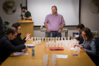 Jason Benedict, assistant professor of chemistry and crystal competition organizer, stands at the head of the table as the judging gets underway.