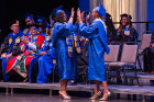 Student speakers Deidree Golbourne (left) and Yanava Hawkins congratulate each other as they pass onstage.
