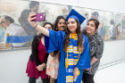 A graduate takes a selfie with friends.