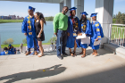 Graduates pose for photos behind the Center for the Arts, with picturesque Lake LaSalle in the background.