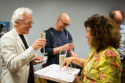 Alumna Gloria Zúñiga y Postigo serves champagne to Barry Smith at a reception celebrating Smith's 65th birthday.