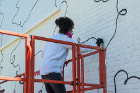 Staff from the Albright-Knox Art Gallery painted the brown brick wall of the former Houdaille Industries building white before Shantell Martin arrived to paint her signature black lines. Photo: Bruce Jackson