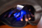 A black light shows the germs that remain on this camper's hands, despite handwashing. Photo: Meredith Forrest Kulwicki