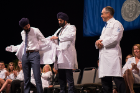 Saarang Singh being coated by his older brother Dr. Harpartap Singh. With Keynote speaker Dr. Robert Ablove to the far right.