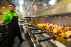 A worker tends to rotisserie chickens at a food preparation station in Crossroads Culinary Center in the Ellicott Complex. Photo: Meredith Forrest Kulwicki
