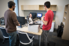 IT Support Specialist Mackenzie Lynch (seated) chats with graduate student Joe Costa (brown sweater) and user support specialist Spencer Miliotto while installing computer equipment.