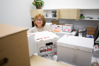 Health Sciences senior staff assistant Bernadine Macy begins unpacking boxes.