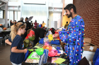 "Giving a demo on antibiotics and how they can be harmful to one's g-i tract and immune system is Nick Bhasin, dressed as ""a microbe."" He is a P1 at U.B. At his table are siblings Mia Muscato, age 9, and Nicholas Muscato, age 6 (teenage mutant turtle)."