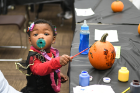 Daionna Stephens, age one, creates pumpkin art.