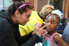 Jackie Giamm, who works at Mercy Hospital E.R. as a P.A., doing volunteer Halloween makeup on Anari Stokes (pink princess).