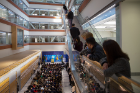 Attendees line the upper level railings surrounding the atrium during the grand opening ceremony.