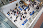 View from overhead looking down on refreshment tables decked out in blue and white tablecloths as attendees mingle.