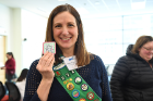 Lauren Kuwik, clinical instructor in the Department of Medicine, proudly wears her Girl Scout sash and holds a special patch Scouts received for attending the event.