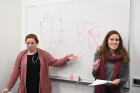 Second-year medical students Teigan Ruster (left) and Cynthia Alvarez draw heart diagrams as part of a lesson on the human heart.