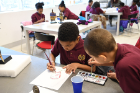 "Raqual a.k.a. ""Rocky"" Adams, age 9 (right), and Joshua Loyd, age 8, add watercolors to their work."