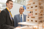 "Michael Paraszczak (left), Architecture student, explains aspects of his model for temporary patient housing called ""Oasis"" to President Tripathi."