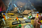 A repairer fixes the motherboard of a cellphone. Note the lack of safety equipment, such as gloves or a mask.