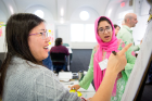 Tu Dam Le (left), a student in the urban and regional planning program, and Midhat Zehra, an undergraduate psychology student, are deep in discussion.