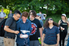 Students look on as Le Wang (left) and Nathan Dubinin prepare to launch the drone.