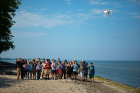 Professors, students and teachers wave at the drone as it takes their photo.