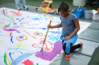 A young girl contributes her talents to a large community painting.