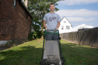First-year student Thomas Barbaccia mows the grass at the Fruit Belt Coalition on Mulberry Street.