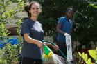 From left: Second-year student Ilana Selli, a member of the orientation committee, and first-year student Neneyo Emmanuel Mate-Kole clean up and water at the Pelion Community Garden.