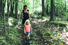 Katie McClain-Meeder hikes through the woods with her daughters Flora (in baby carrier) and Charlotte.