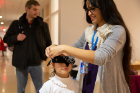 "Destiney Plaza, a first-year graduate student in the School of Management, blindfolds a young participant at the ""program a human"" station."