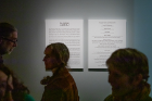 Visitors pass by a description of the exhibition.