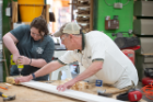 From left, Macy McDonald, a doctoral student in English, and Tom Ulbrich, assistant dean for social innovation and entrepreneurship initiatives, joined the entire cohort of fellows to help the Service Collaborative construct beds for children living in poverty. Photo: Onion Studio.