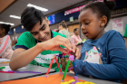 UB environmental design student and Imagine LaSalle volunteer Nofel Sohail helps a child with her design.