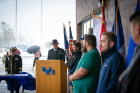 Dan Ryan (at podium), director of veteran services, speaks while student-veterans stand next to their branch flags: (from left) Chanel Powell, Army; Michael Powers, Marines; Justin Downey, Navy; Alexander Nowasell, Air Force; Andrew Cook, Coast Guard; Taylor Ashmore, POW/MIA (out of frame).