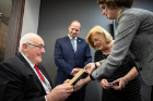 Alison Fraser (far right), assistant curator for the Poetry Collection, presents a book from the Joyce Collection to Irish Sen. Billy Lawless.