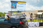 Rasheed Wyatt and April Baskin wave as Pierre Brown's car drives by, his name and photo displayed on the big screen.